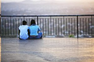 young couple sitting on roof of high rise